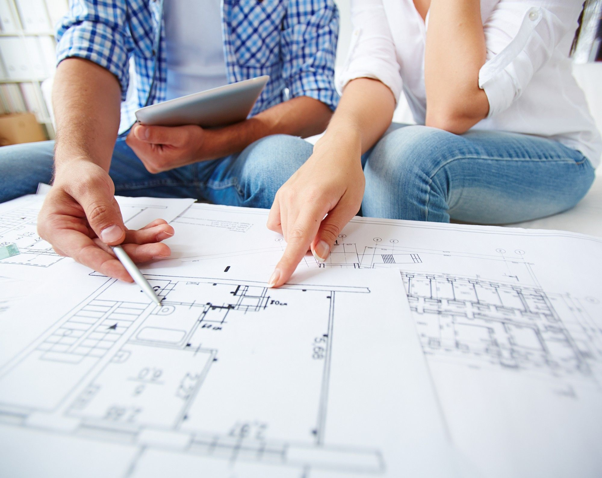 Couple pointing at blueprints